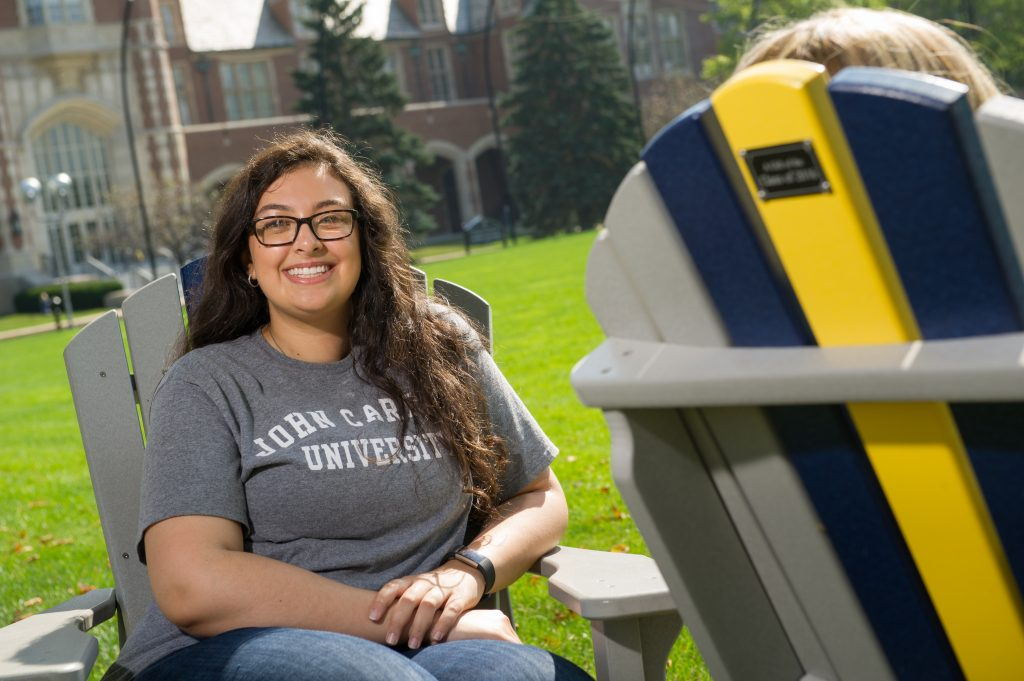 student sitting in chair on campus