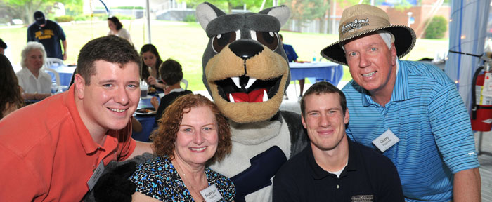 Parents and students smiling with mascot