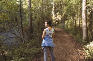 woman standing on a path in the woods
