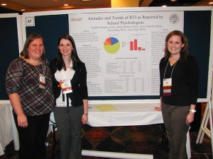Three women posing in front of a board with graphs