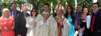 Fr. Alan Vince Benander following his ordination to the priesthood with his family and ordaining Bishop Vann.