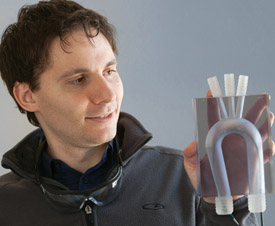 Malinskiy holds a 1-to-1 aortic arch model with a cardiac catheter inside it.