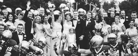Elizabeth Spirk and Vince Doorhy '08, along with their wedding party, pose for a photo with the JCU football team.