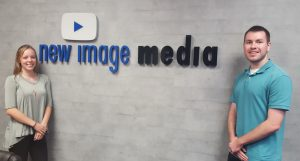 Photo of Julianna Clark and Benjamin Troy in front of a New Image Media sign
