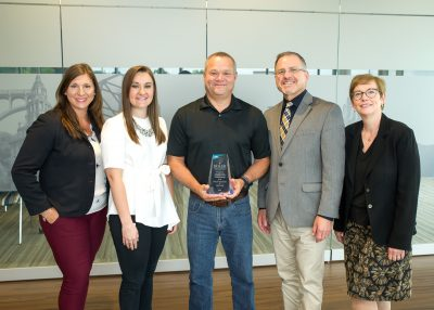 Brandi Mandzak, Jennifer Sloat, Mike Quinn, Al Miciak, and Laura Atkins smile with the award