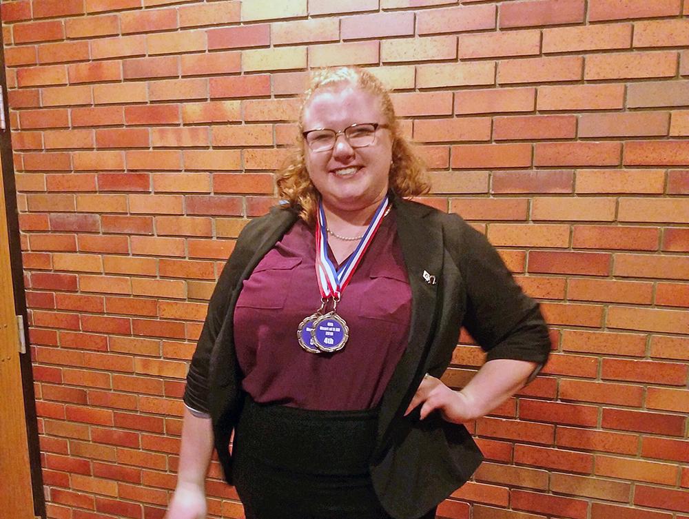 Megan standing, wearing medals