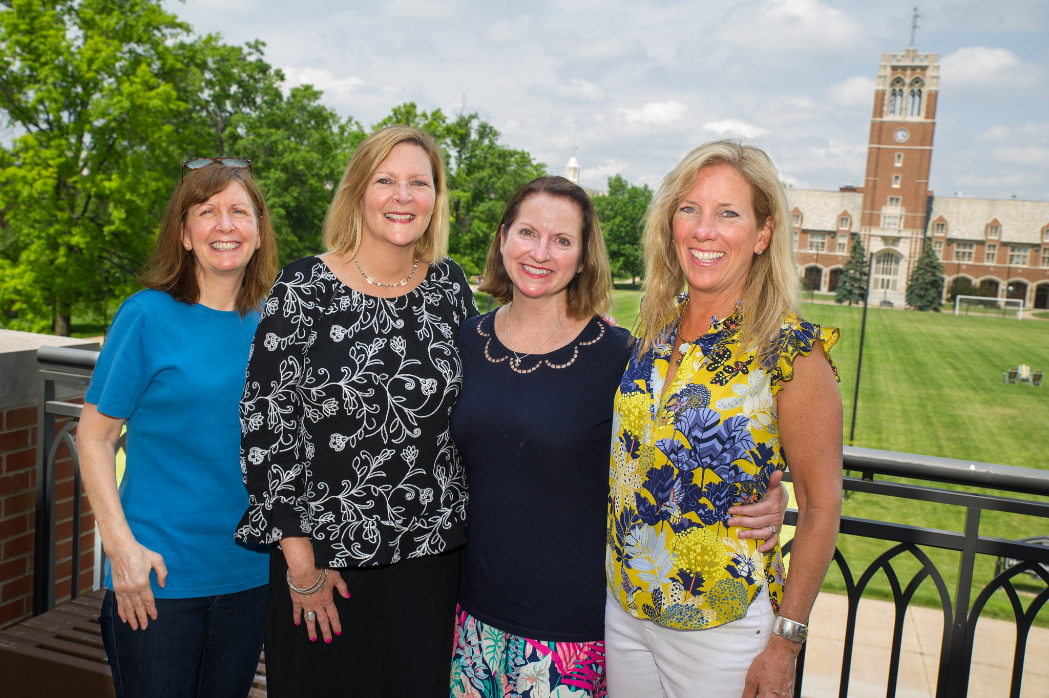 Four female alumni stand on the balcony and smile with the bell tower in the background.