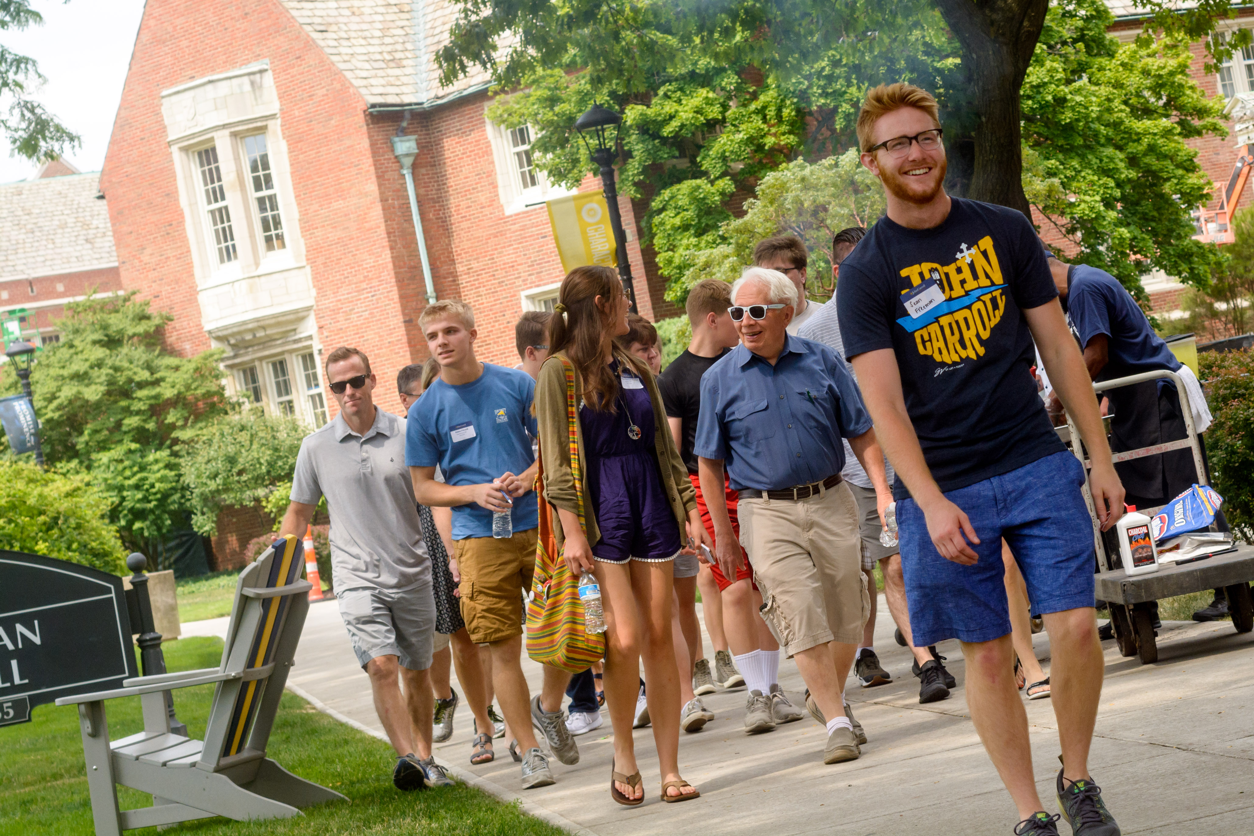 c8e4e66041 Groups of students and families smile and walk in front of Dolan Hall near  the Quad