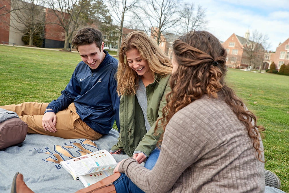 Three students sit on a blanket on the Hamlin Quad and study