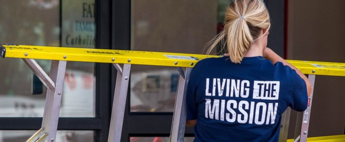 Student wearing Living the Mission shirt and volunteering